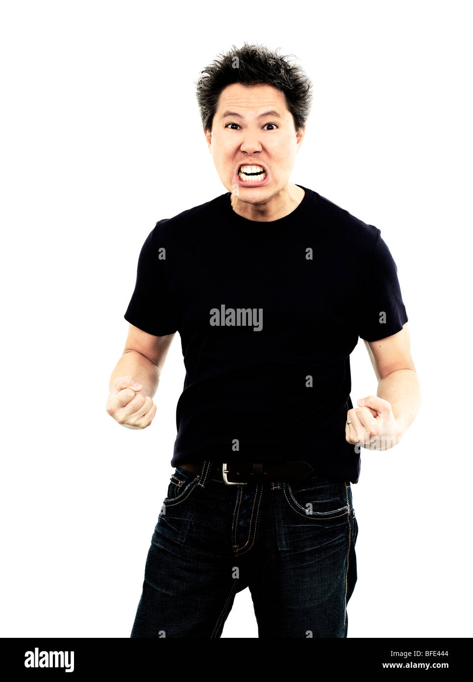 44 year old Asian male wearing jeans and a blue t-shirt standing against a white background screaming - Stock Image