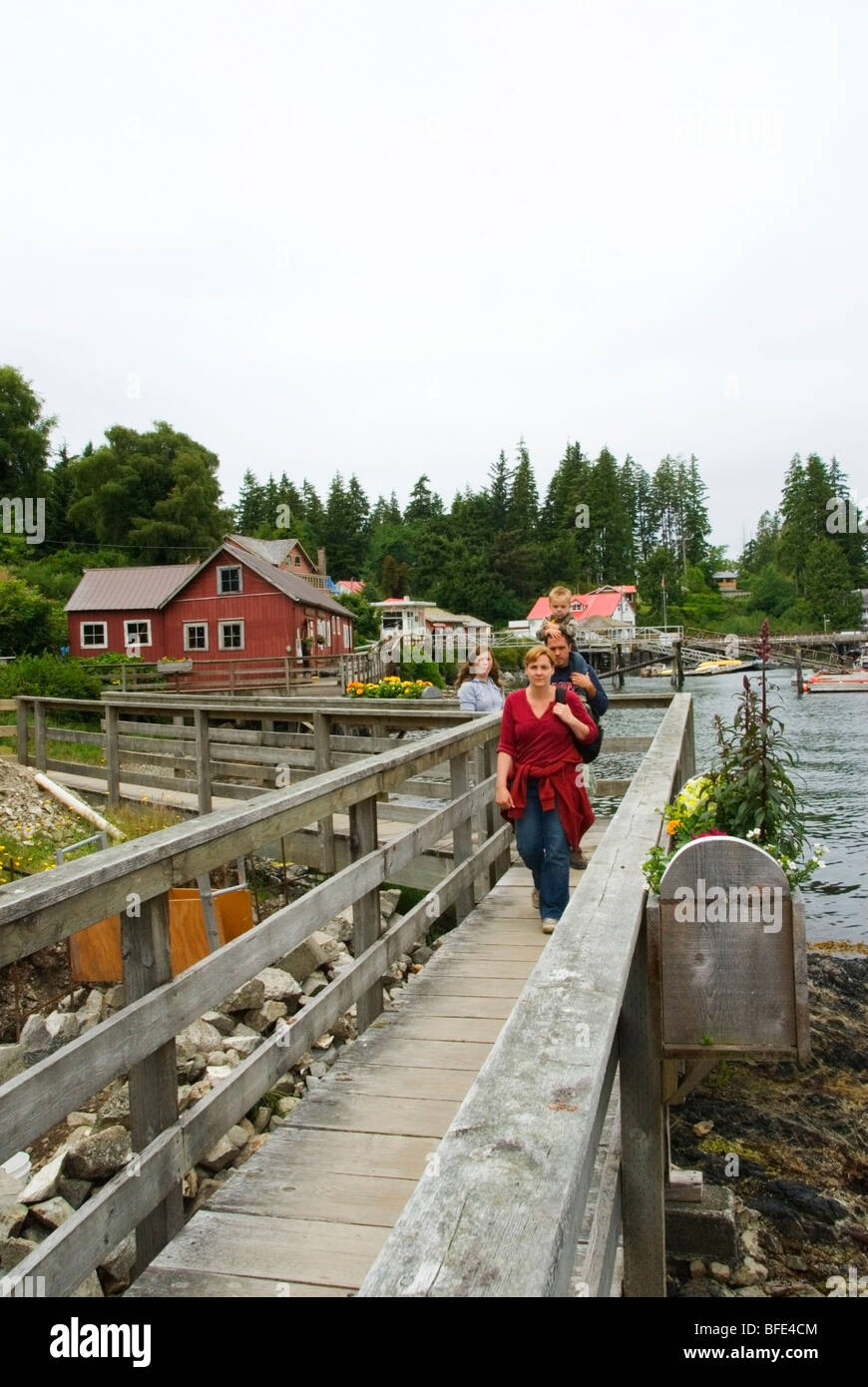 A family on seaside boardwalk in the coastal village of Bamfield, Vancouver Island, British Columbia, Canada Stock Photo