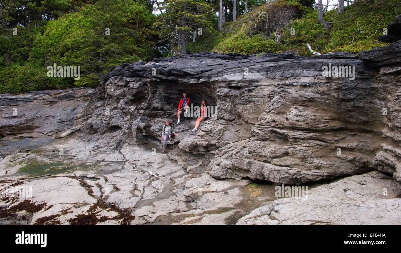 Beachcombers rest in a natural beach cave along the Juan de Fuca Marine Trail on Vancouver Island, British Columbia, - Stock Image