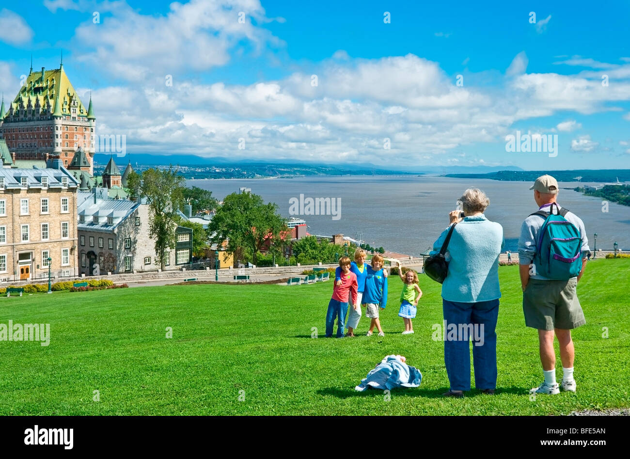 Souvenir photo of family in front of Chateau Frontenac and the St. Lawrence River, Quebec City, Quebec, Canada - Stock Image