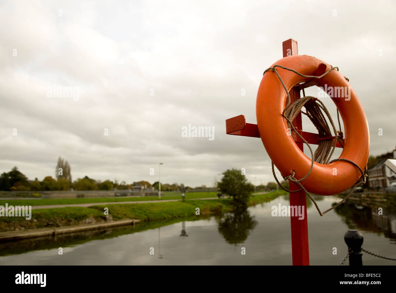 life saving ring next to canal on a cloudy day - Stock Image