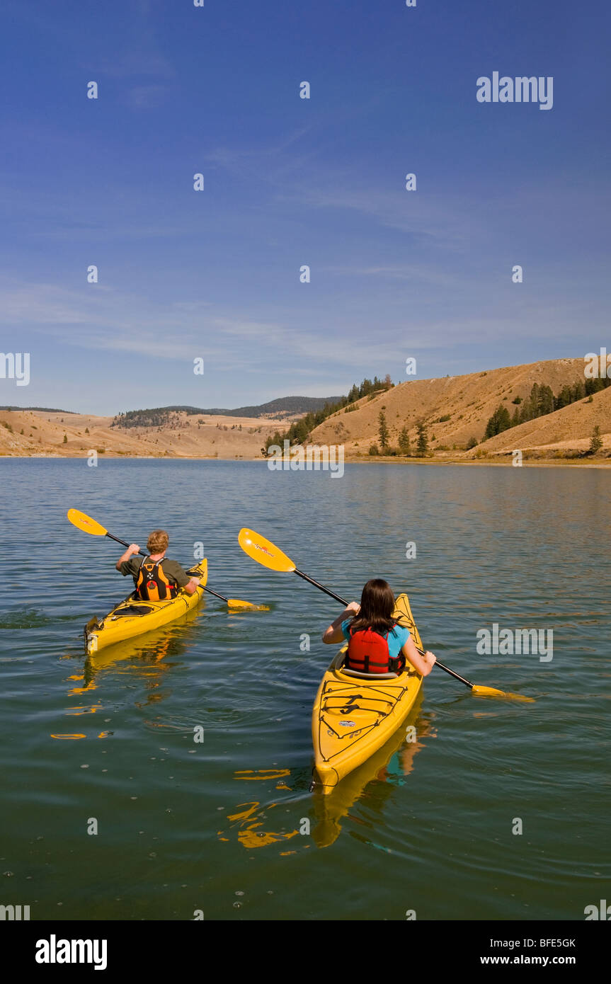 Two kayakers paddle in Trapp Lake on a stellar day, just south of Kamloops, British Columbia, Canada - Stock Image