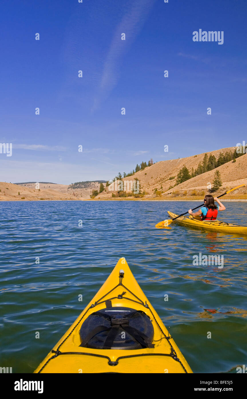 Young woman kayaking on a stunning day at Trapp Lake near Kamloops, British Columbia, Canada - Stock Image