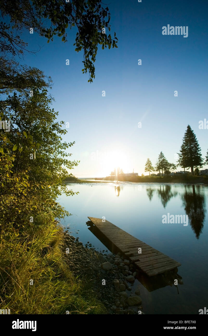 River at sunrise and an aging dock lend an air of tranquility to scene Oyster River Black Creek Vancouver Island - Stock Image
