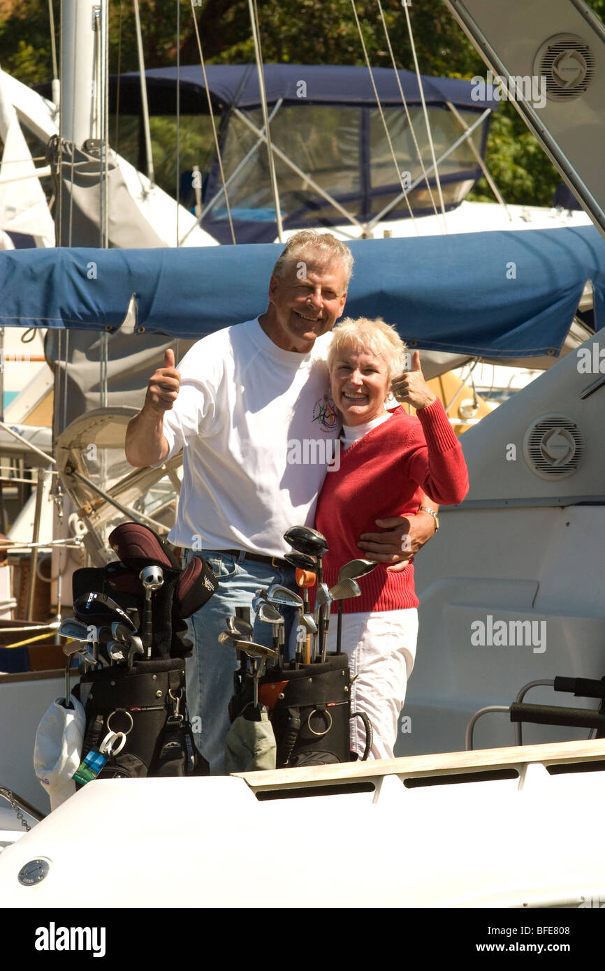 Baby boomers with golf clubs having just arrived via sailboat head out for a day of golf Salt Spring Island Gulf - Stock Image