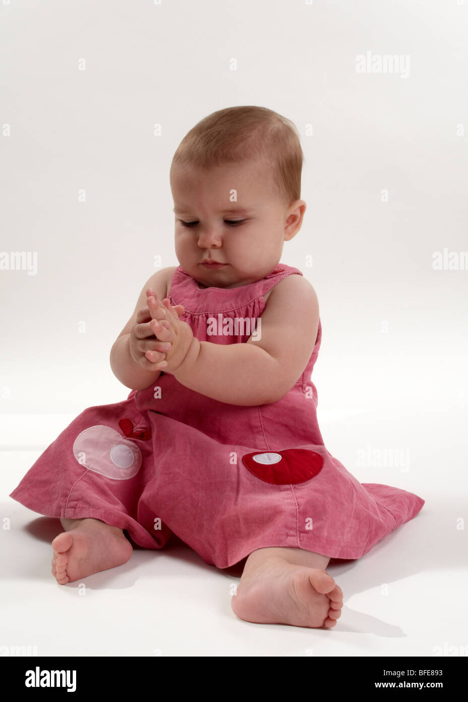 1 year old baby girl in pink dress on white background stock photo