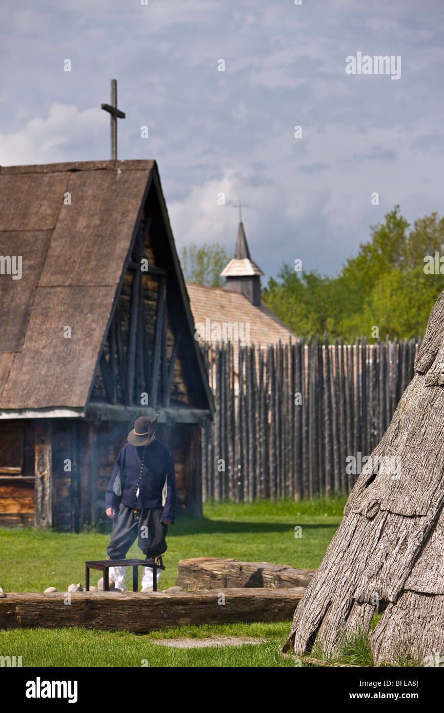 Costumed character tending a fire in the Sainte-Marie Among the Hurons settlement in the town of Midland, Ontario, - Stock Image
