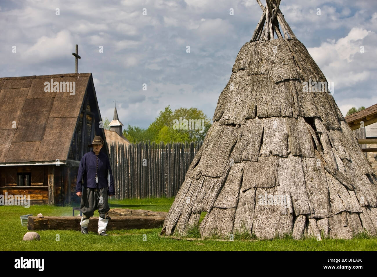 Costumed character next to a teepee in the Sainte-Marie Among the Hurons settlement in the town of Midland, Ontario, - Stock Image