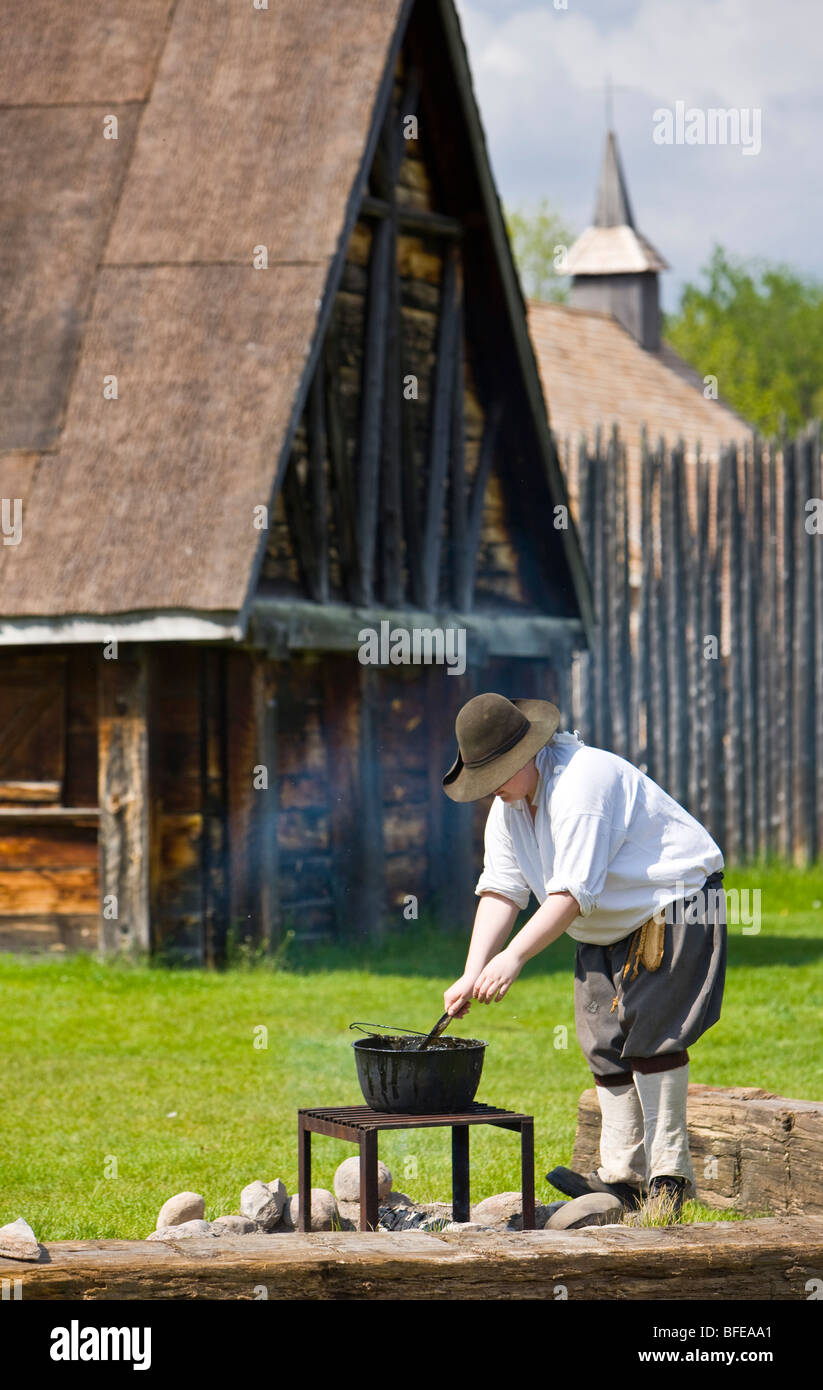 Costumed character tending a pot over a fire in Sainte-Marie Among Hurons settlement in town of Midland Ontario Stock Photo