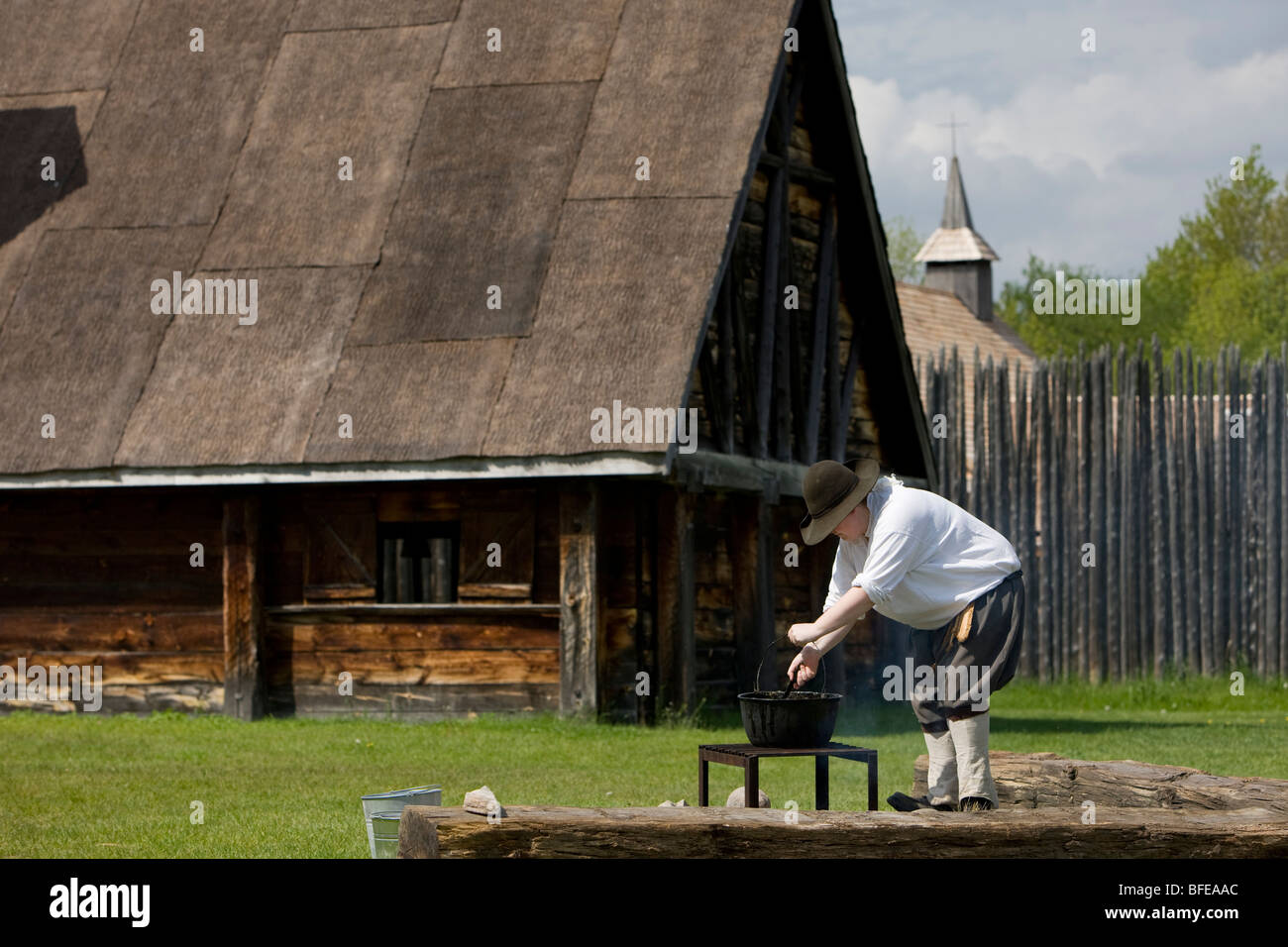 Costumed character tending a pot over a fire in Sainte-Marie Among Hurons settlement in town of Midland Ontario - Stock Image