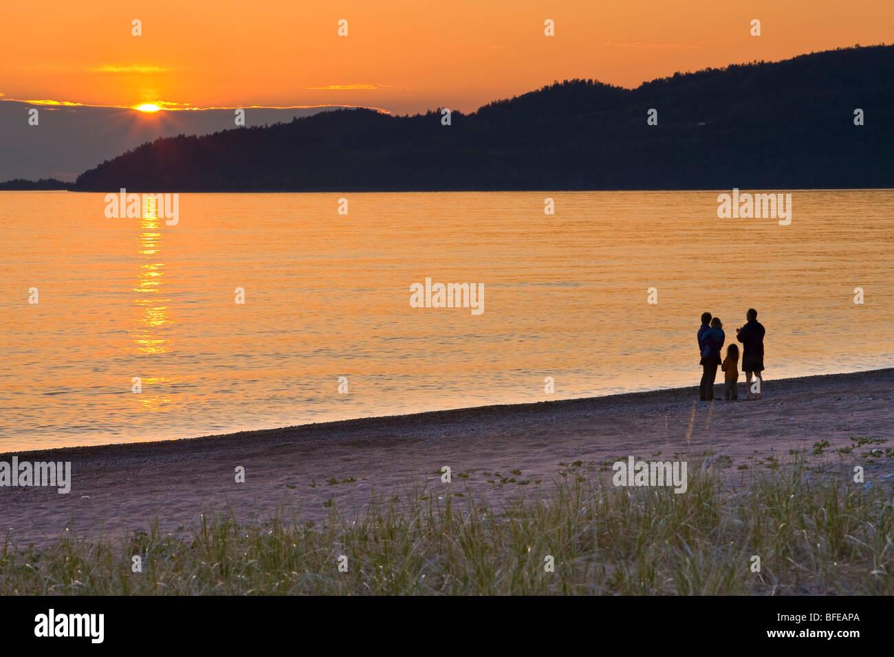 Family walking along the beach at Agawa Bay at sunset, Lake Superior, Lake Superior Provincial Park, Ontario, Canada - Stock Image
