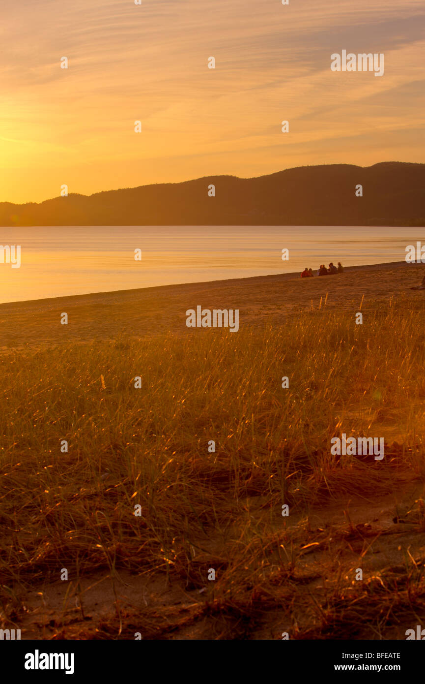 Group of people relaxing on the beach at Agawa Bay at sunset, Lake Superior, Lake Superior Provincial Park, Ontario, - Stock Image