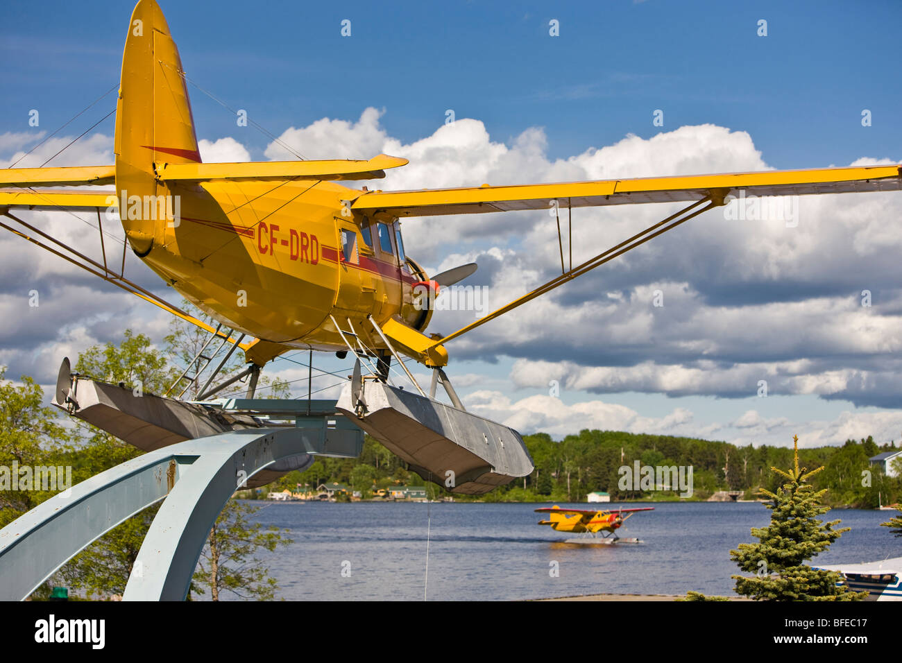 Norseman aircraft on a pedestal in Norseman Heritage Centre Park with an active Norseman Chimo Air Service taxiing - Stock Image