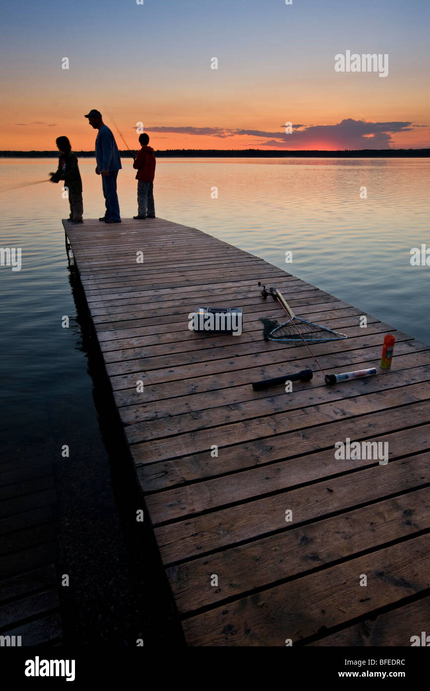 A father with his two sons fishing at the end of a wharf on Lake Audy at sunset, Riding Mountain National Park, - Stock Image