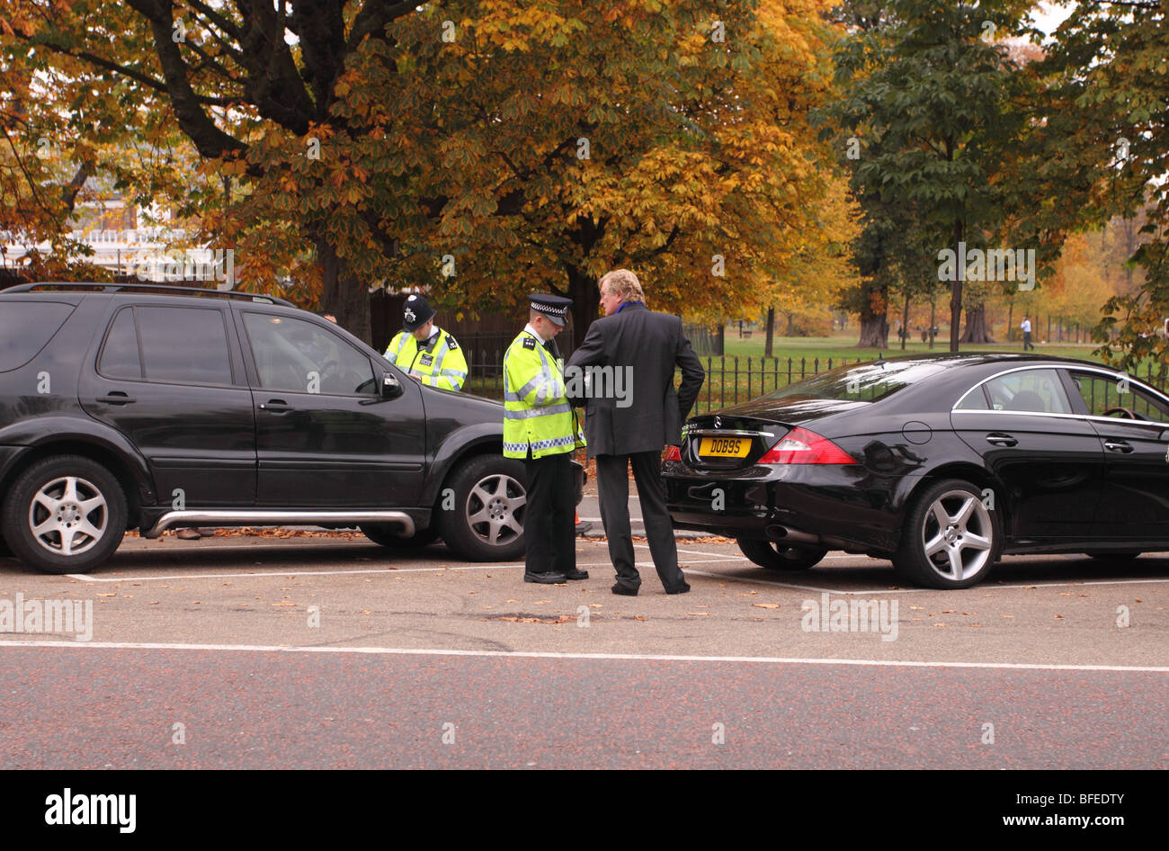 Metropolitan Police Officer talking to a car driver along West Carriage Drive in Hyde Park London EDITORIAL USE - Stock Image