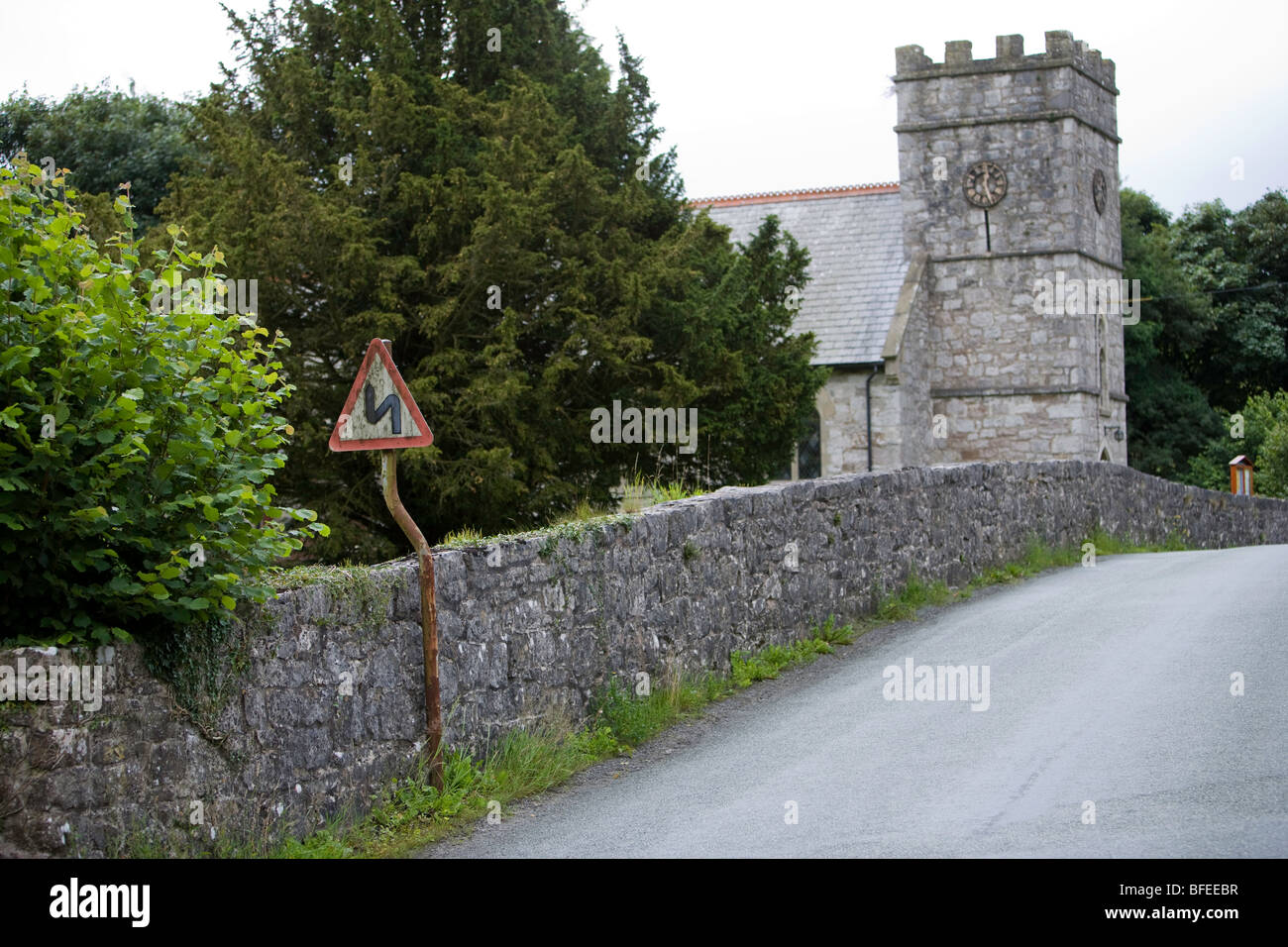 Church nead double bend first to the left road sign. Crooked sign on crooked post. Pen-y-Dyffryn. Wales. United - Stock Image