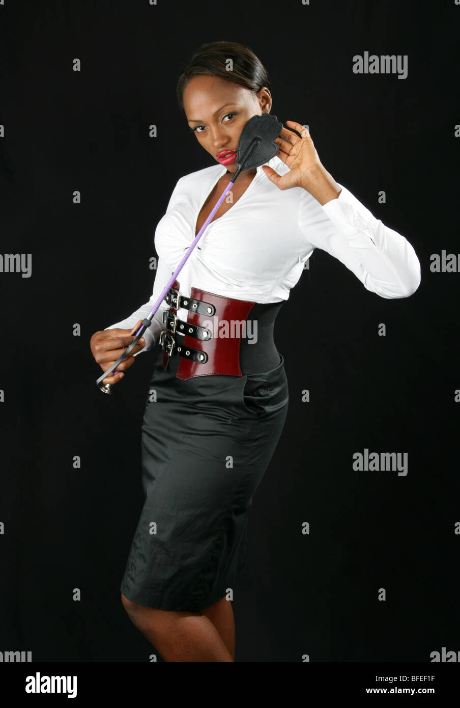 African Woman Wearing a White Blouse, Black Skirt, Leather Corset and  Holding a Paddle. Fetish Mistress.