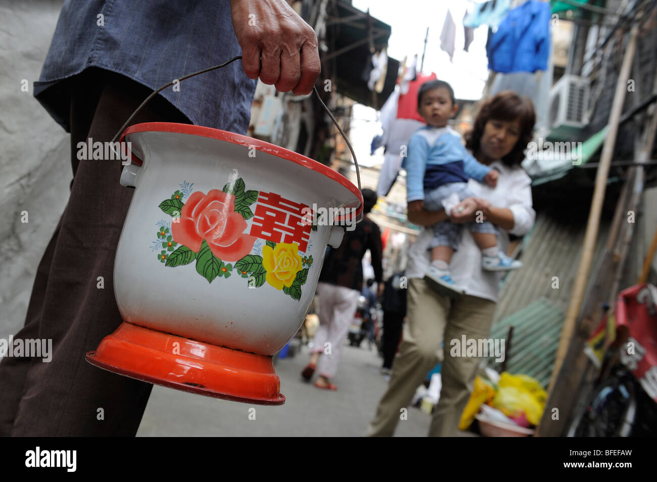 A man with a chamber pot in a Shikumen Lane in Shanghai, China. 19-Oct-2009 - Stock Image