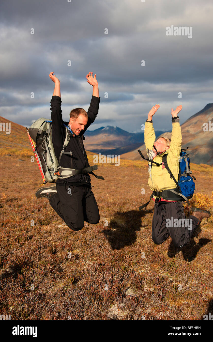 Hikers jumping in the tundra at sunset, Tombstone Territorial Park, Yukon, Canada - Stock Image
