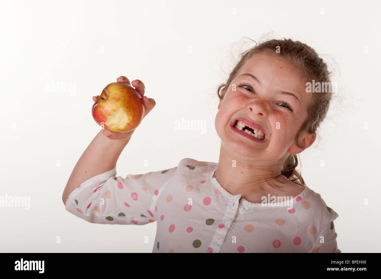 little girl (7 years old) who is missing front teeth eating apple on red bean bag chair against - Stock Image