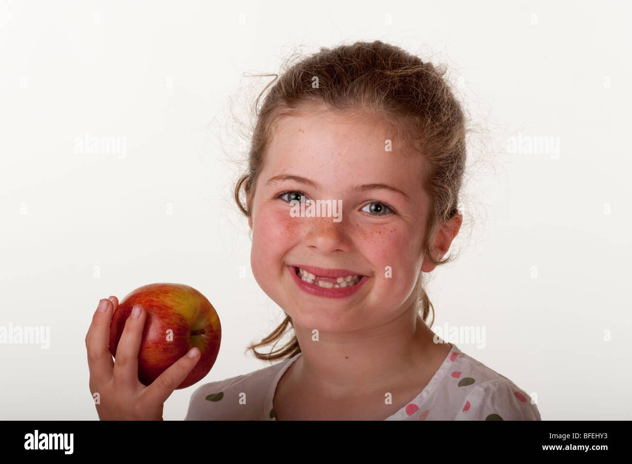 little girl (7 years old) who is missing front teeth eating apple on red bean bag chair against white background - Stock Image