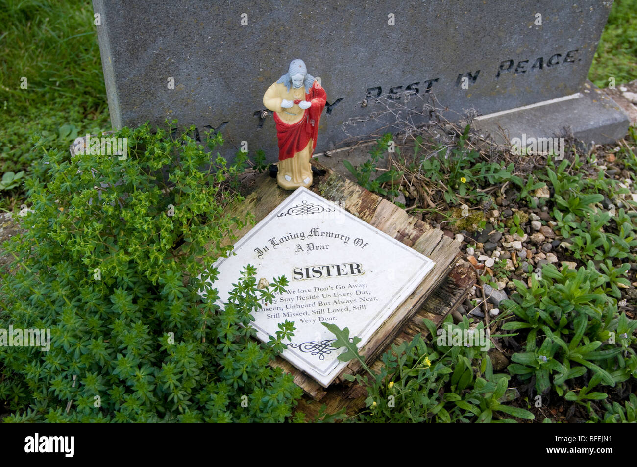 A plastic statue on an grave in an Irish cemetery - Stock Image