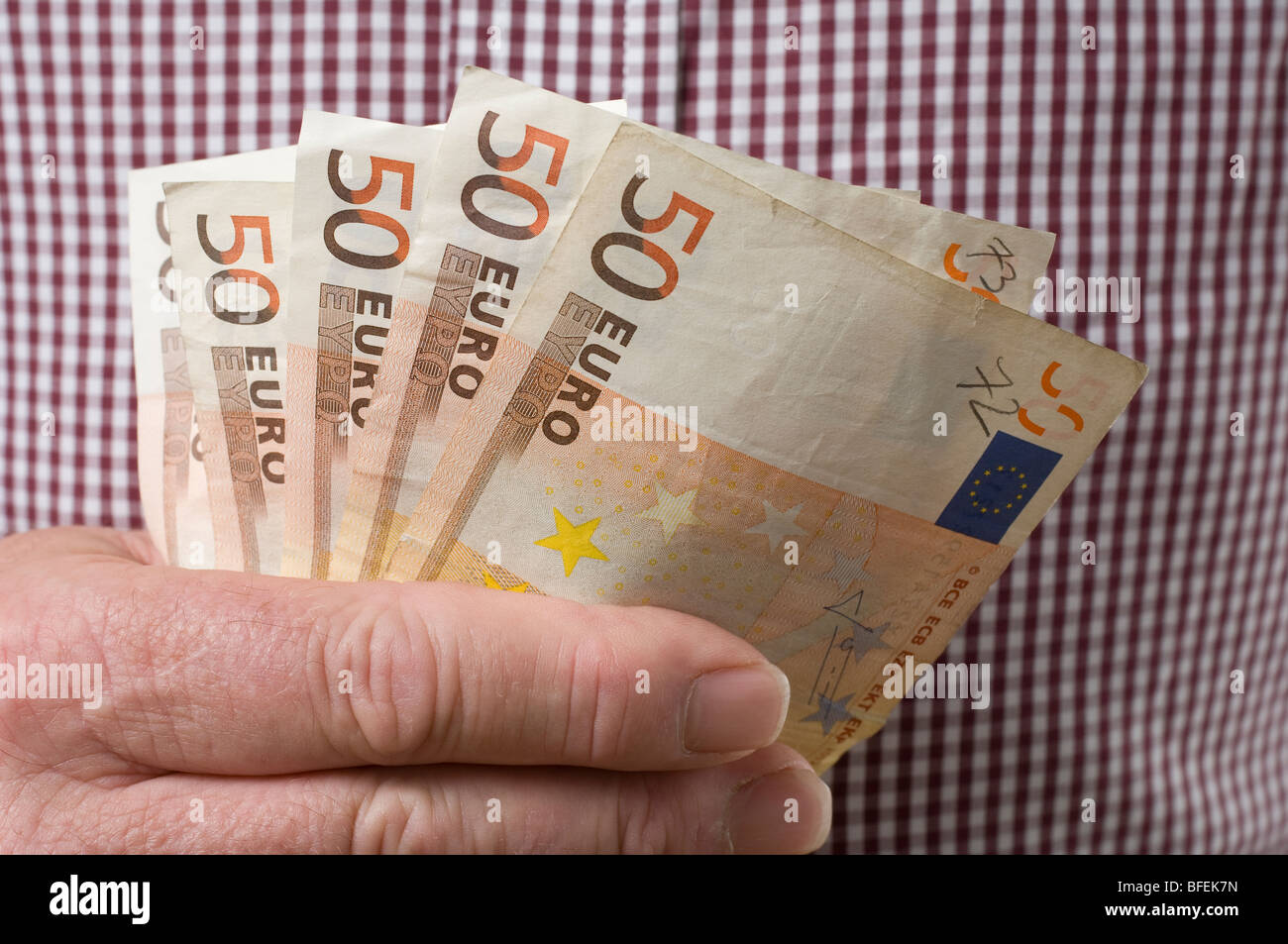 A poker hand of used Euro banknotes .- A man's hand holding Euro banknotes. - Stock Image