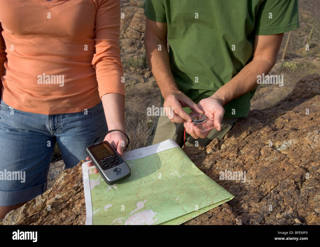 Couple using GPS, compass, and topo map while hiking. - Stock Image