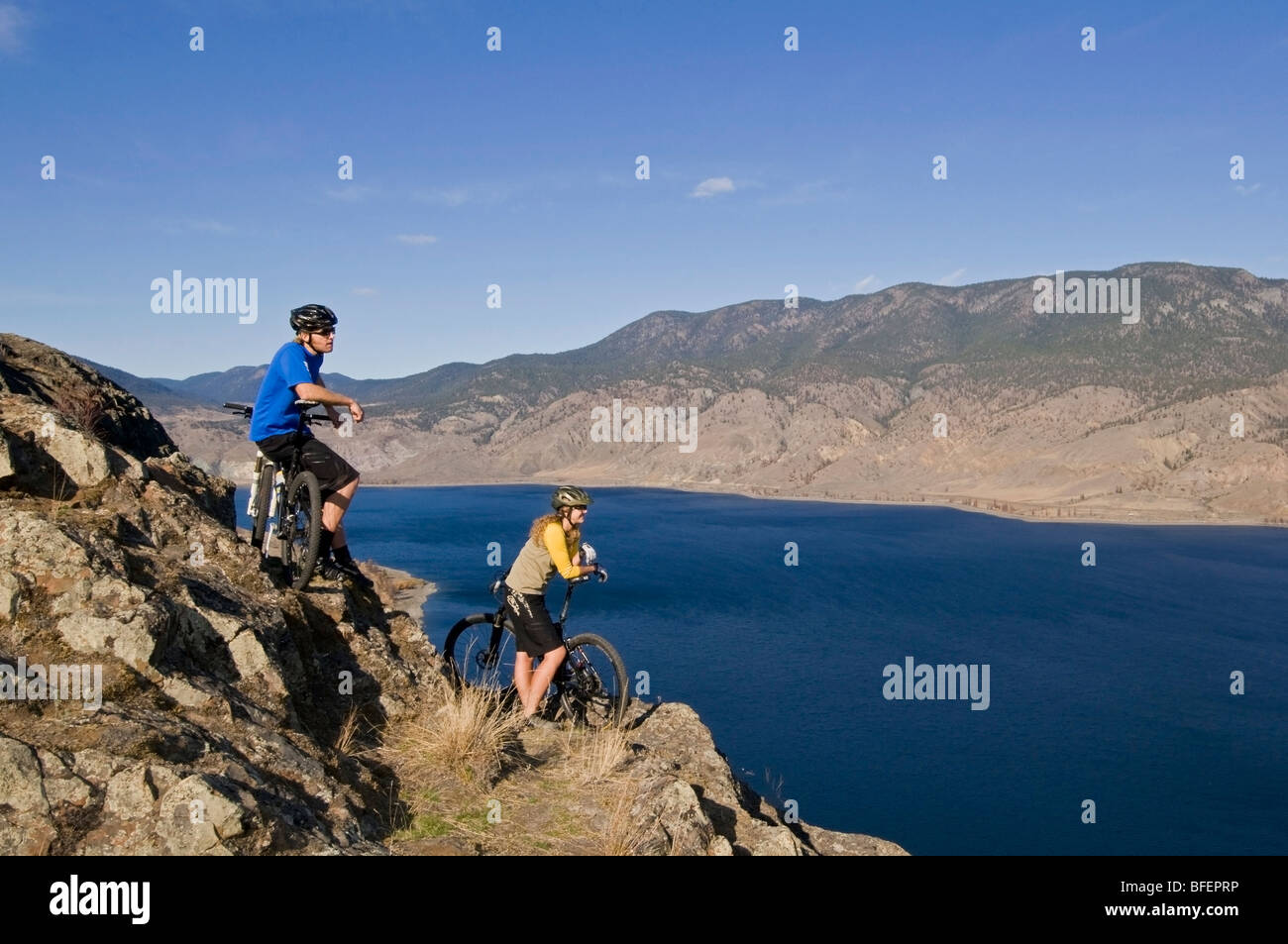 Young couple enjoying view of Kamloops Lake while mountain biking on a beautiful day just west of Kamloops British - Stock Image