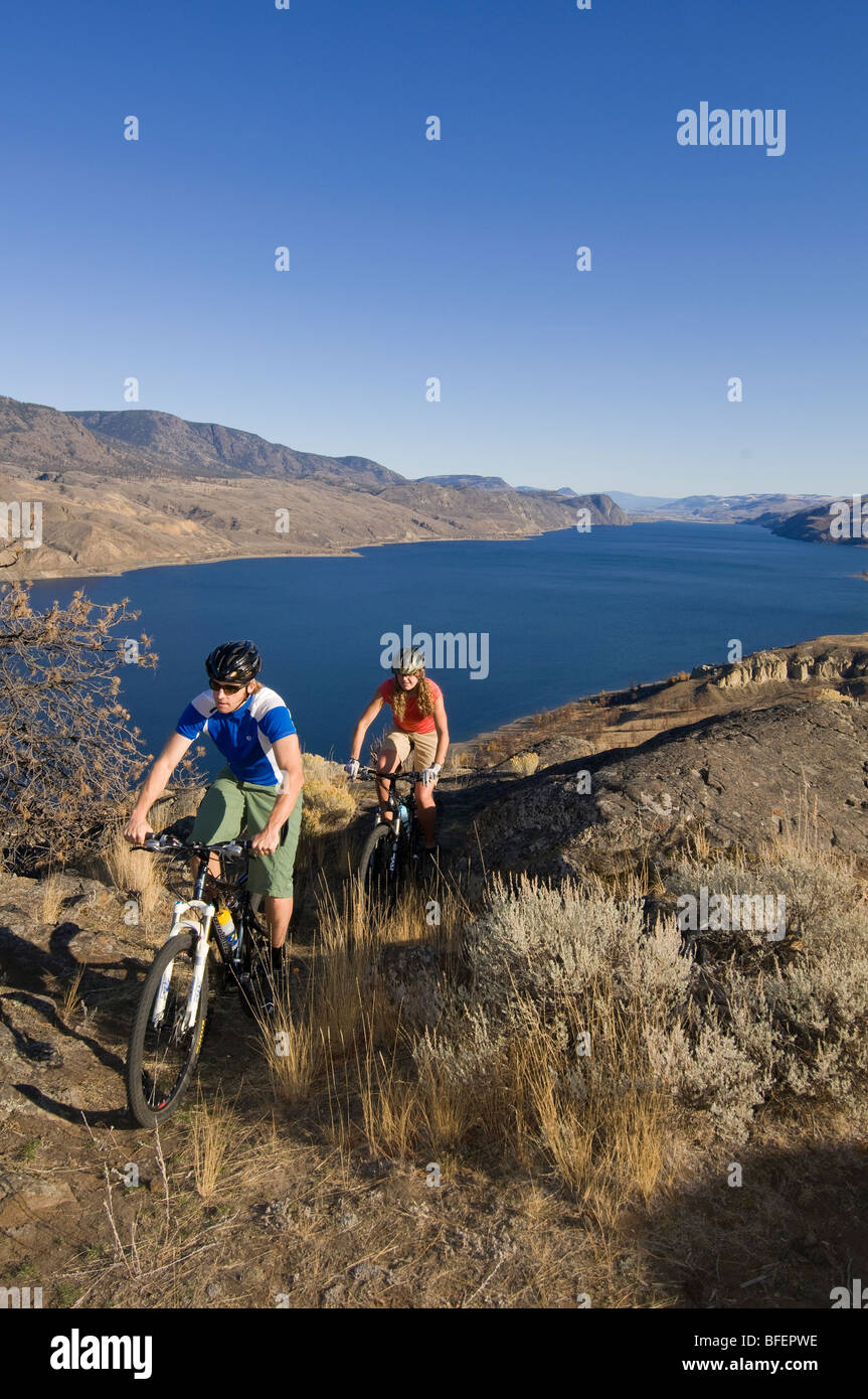 A couple mountain biking in summer by Kamloops Lake, just west of Kamloops, British Columbia, Canada - Stock Image