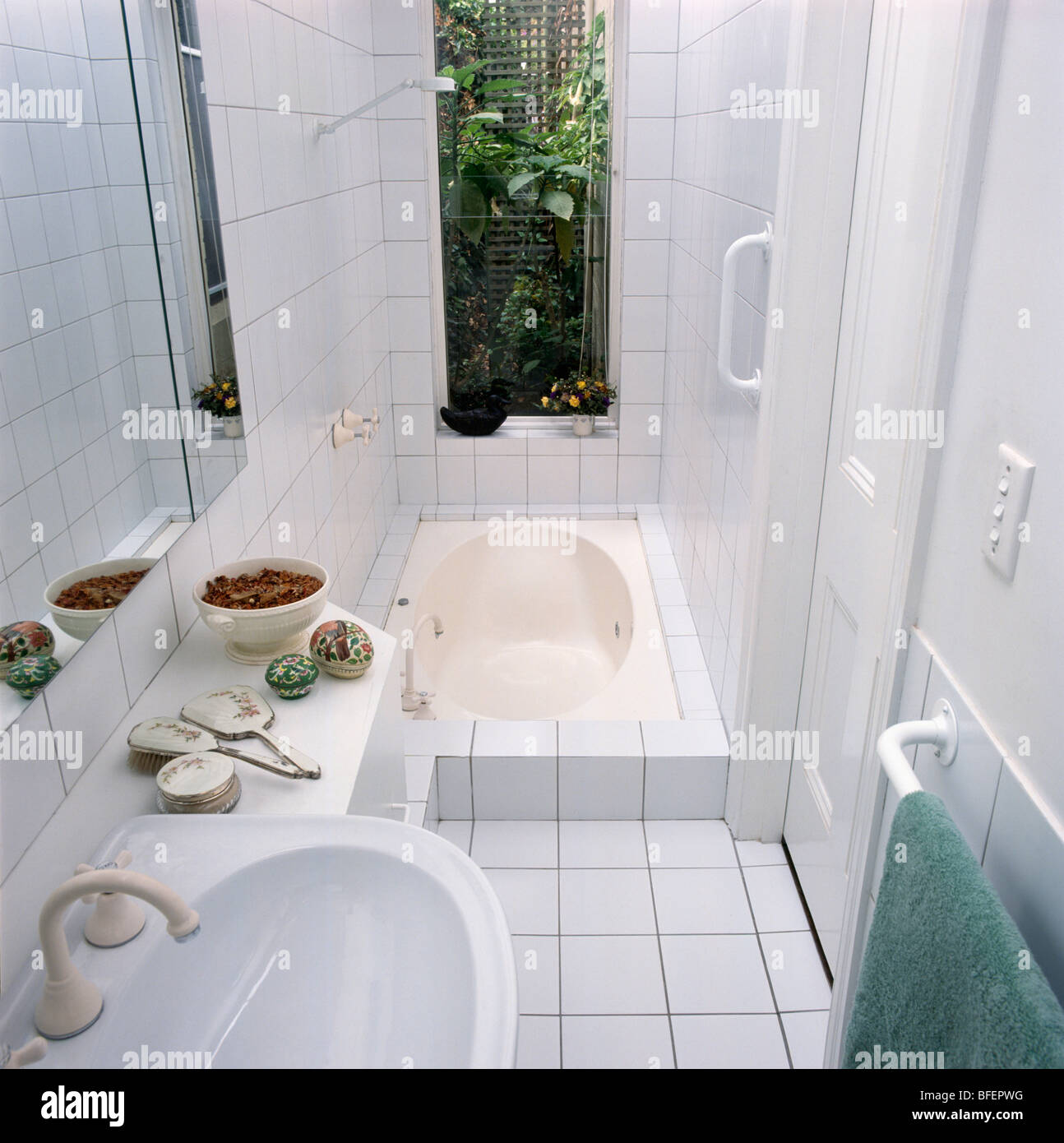 Window above sunken bath in small white tiled modern bathroom Stock ...