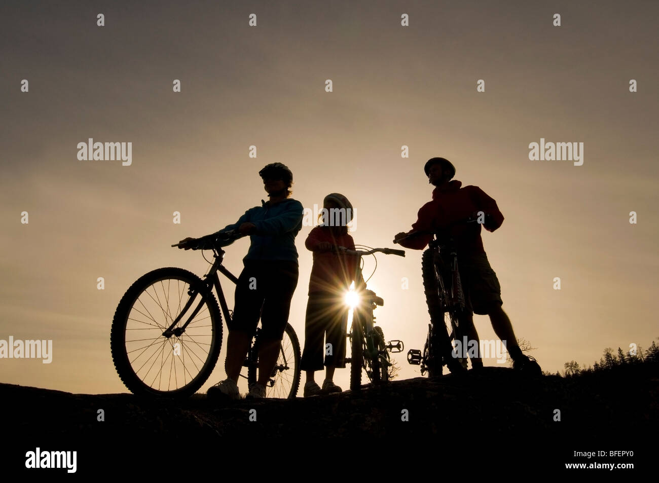 Silhouette of a family taking in the view over Kamloops Lake while mountain biking, west of Kamloops, British Columbia, - Stock Image