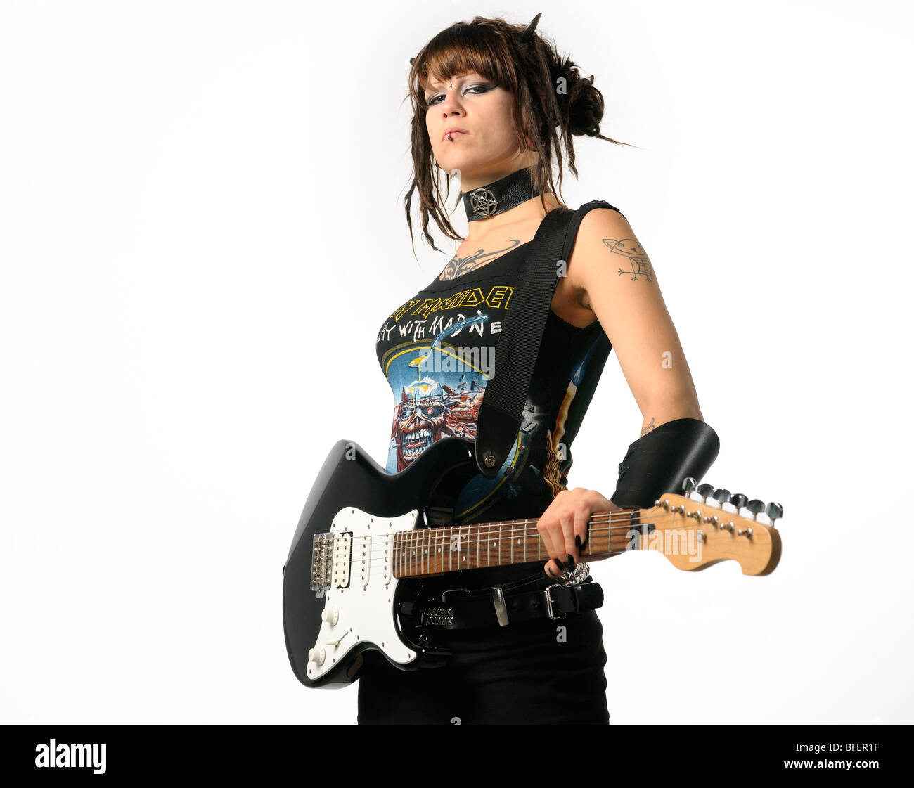 Heavy Metal chick with horns and tattoos holding a black guitar on a white background - Stock Image