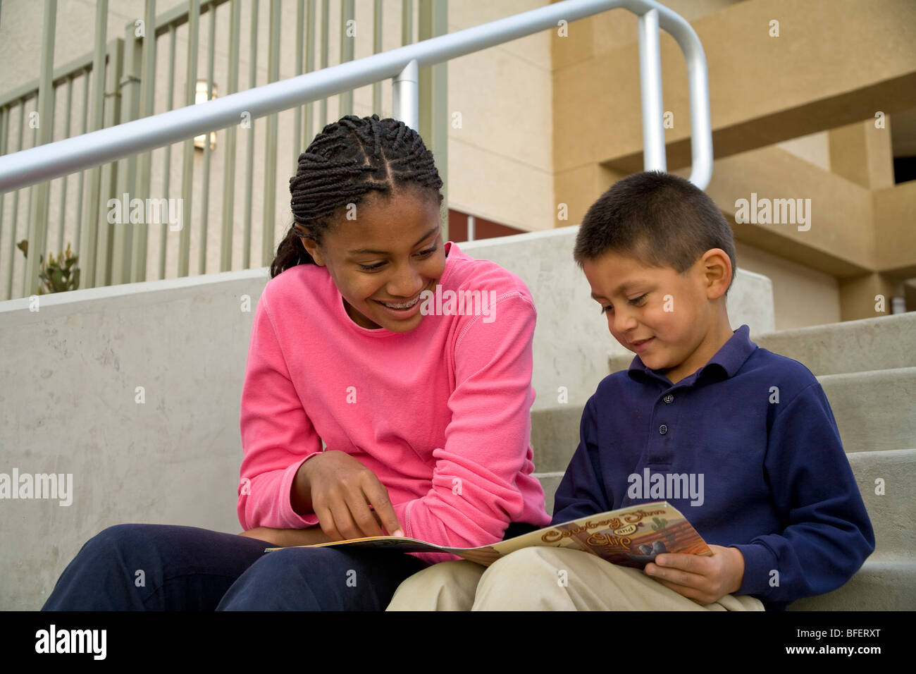 African American teen girl reads a book to an Hispanic boy on steps child helping another diverse diversity California - Stock Image