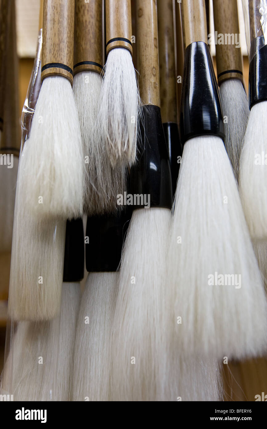 Calligraphy brushes hanging in shop. - Stock Image