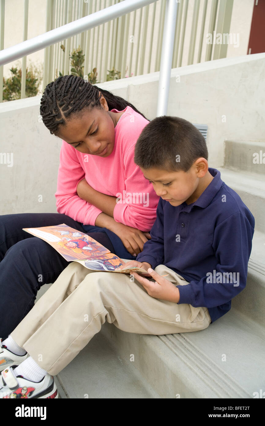 young person people Multi ethnic ethnically diverse teenage girl reads book Hispanic boy steps mentor mentoring - Stock Image
