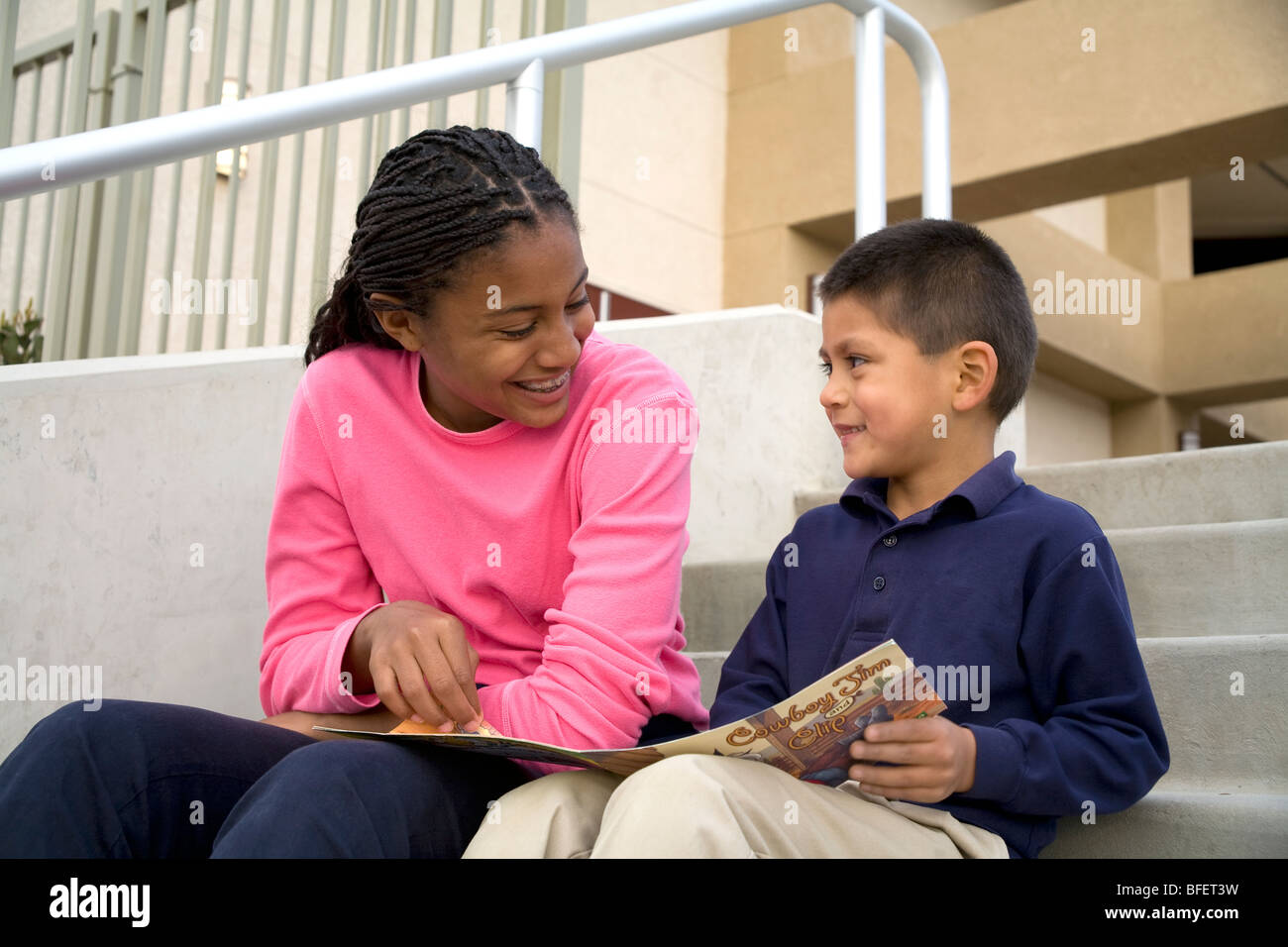 Older teenage girl reads a book talks smiling smiles encouraging encouragement boy 5-6 years old United States MR - Stock Image