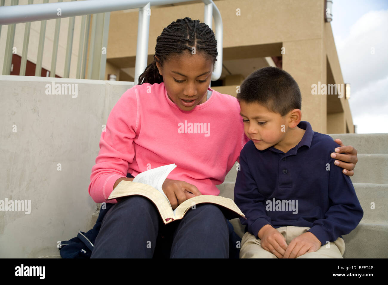 multiethnic multi racial diversity racially diverse multicultural girl 13-14 year years old reads Bible to boy 5 - Stock Image