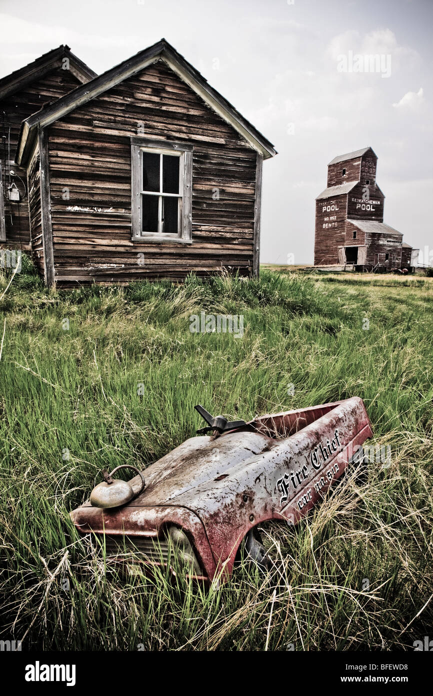 Abandoned farm town with child's pedal car, Bents, Saskatchewan, Canada - Stock Image