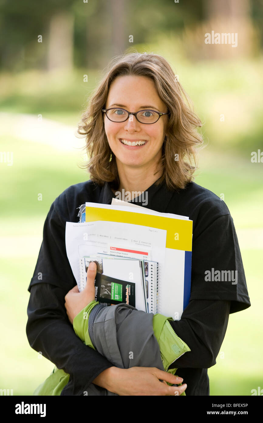 A college student, on orientation day at North Island College, holds her books and study material for the upcoming - Stock Image