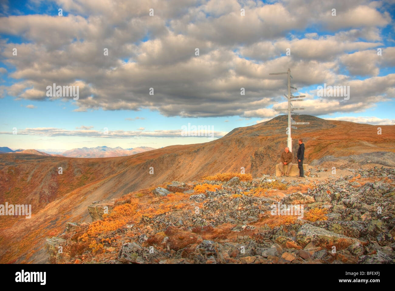 Two people, father and son standing at the signpost on top of Keno hill, Yukon. The Werneke mountains are oin the - Stock Image