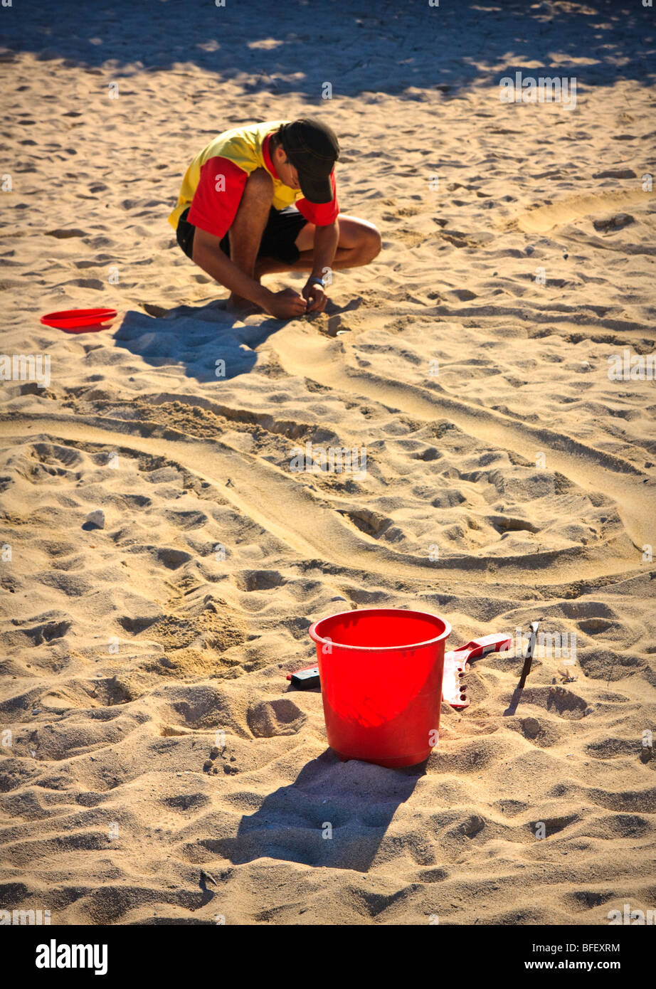 Vacation resort employee preparing bucket and markers for a contest, sandy beach, Cuba - Stock Image