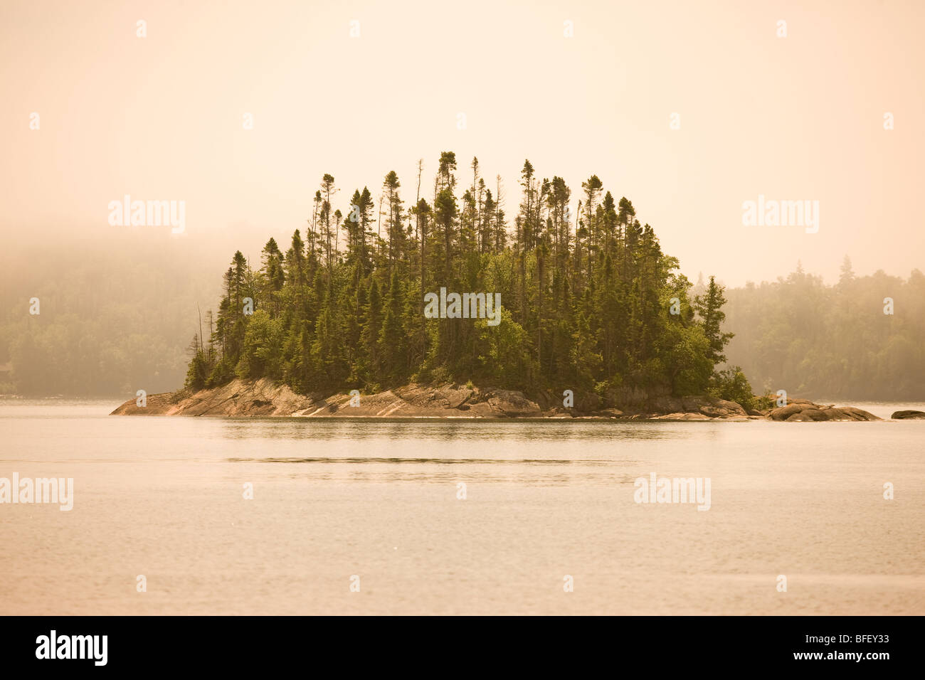 Island in fog in Warp Bay as seen from a canoe/kayak or hike-in campsite along Lake Superior Coastal Trail Lake - Stock Image