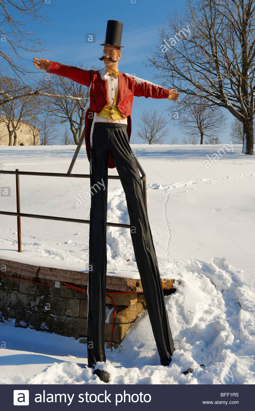 Clown on stilts at the Citadella park in the snow . Budapest, Hungary - Stock Image