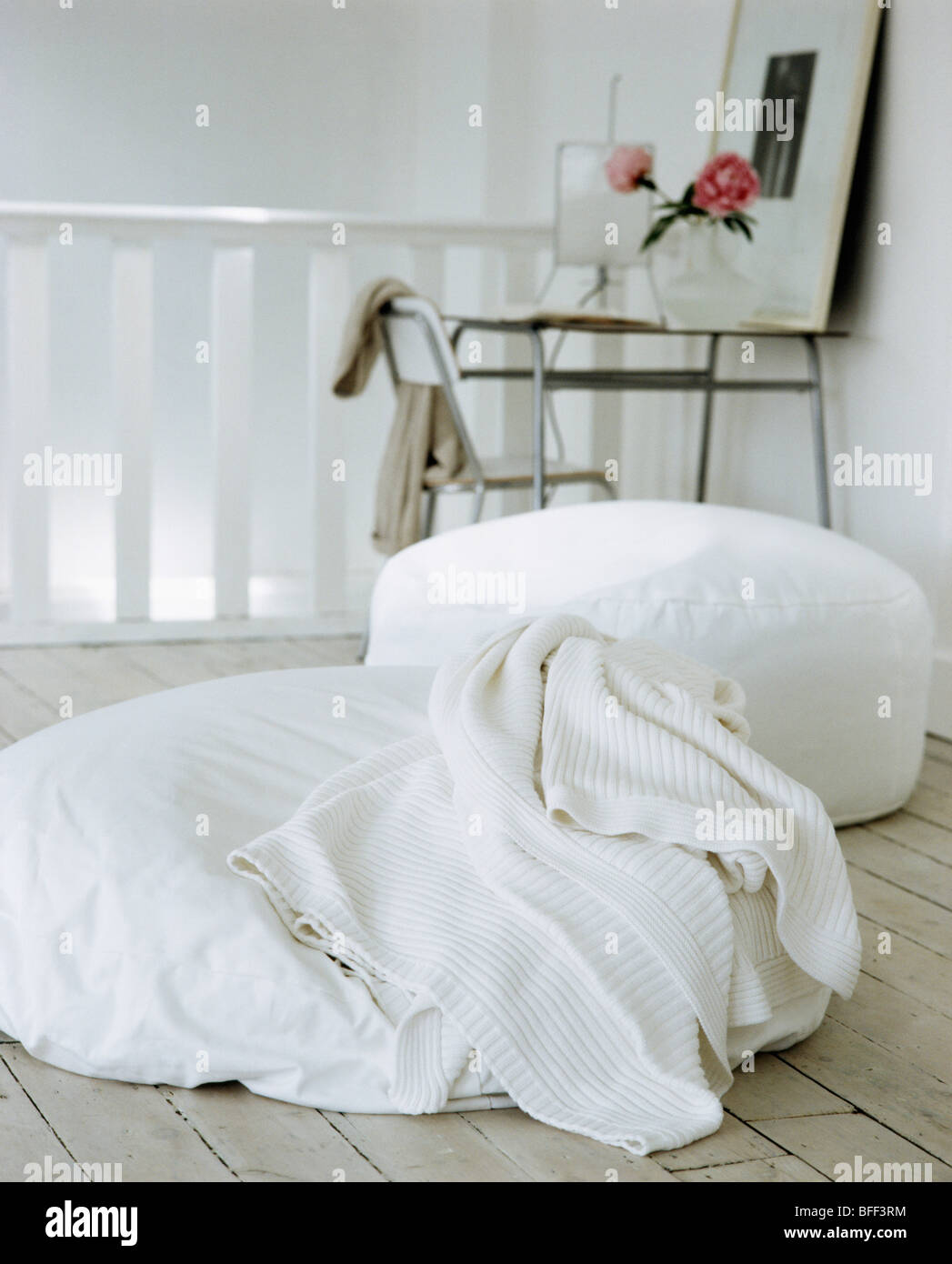 Close-up of white wool throw and large white floor-cushions on ...
