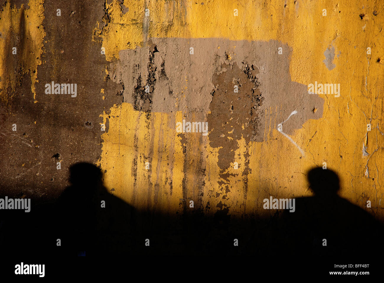 Yellow wall with silhouettes of two people - Stock Image