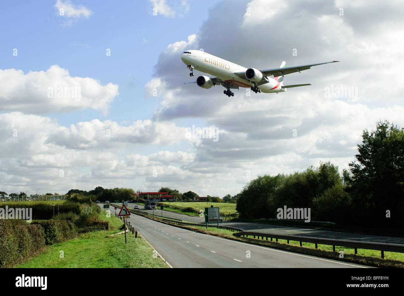 Boeing 777 operated by Emirates crosses the A45 dual carriageway on approach for landing at Birmingham Airport - Stock Image