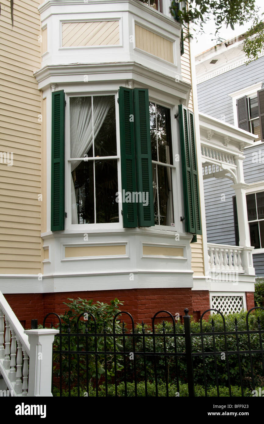 details of a historic Victorian home including wrought iron fence, green shutters, ornate details on side porch - Stock Image