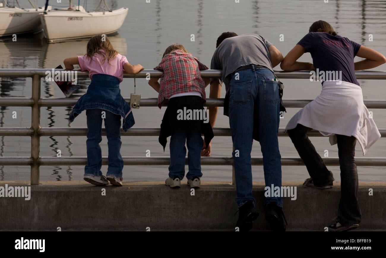 A family in Milwaukee, Wisconsin leans over a railing to look at something in Lake Michigan. - Stock Image