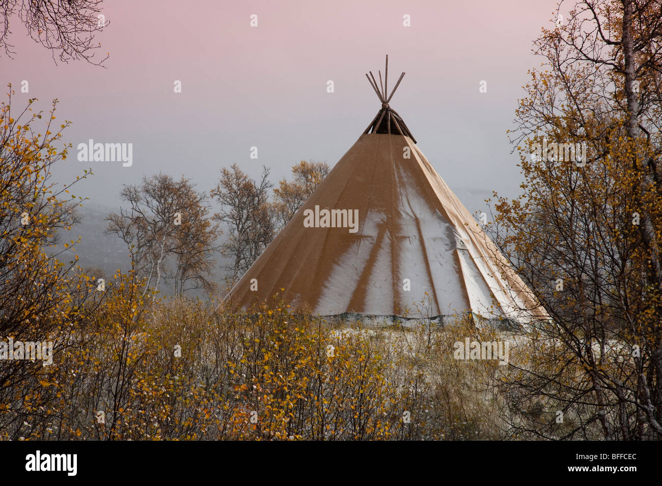 Traditional sami hut tent cot and birch forest in autumn with first snow and view over snowy forest - Stock Image